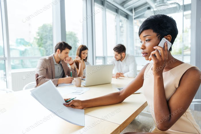 Serious businesswoman with documents talking on cell phone in office
