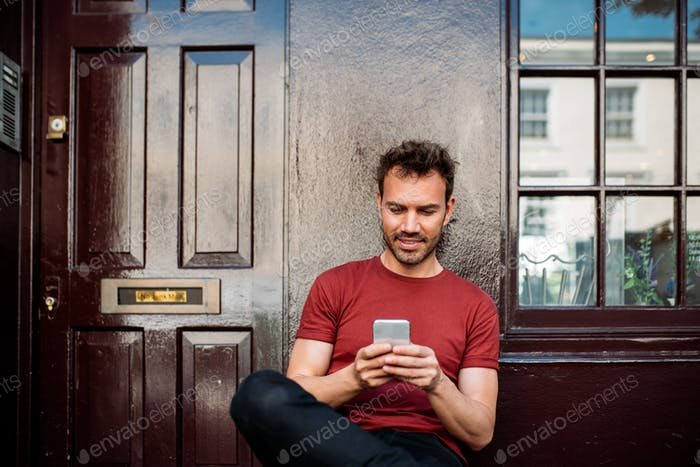 Man sitting in a bench on a beautiful maroon background