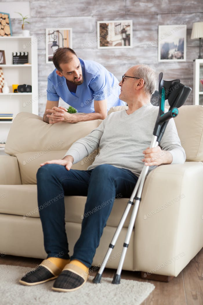 Senior man sitting on couch with crutches in nursing home