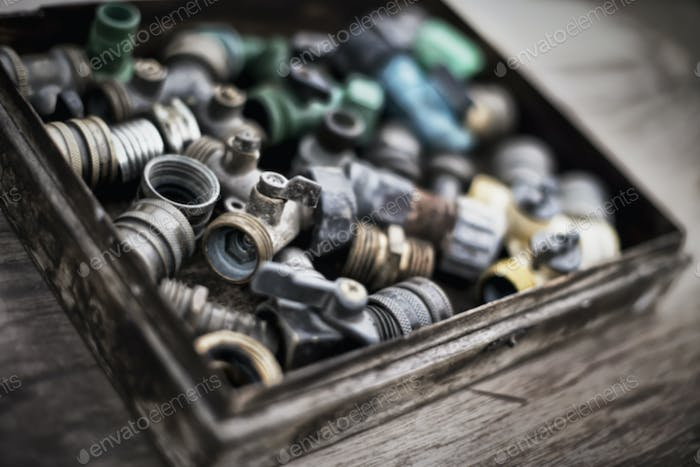 Washers and hose pipe joint fittings in a wooden box in the greenhouse.