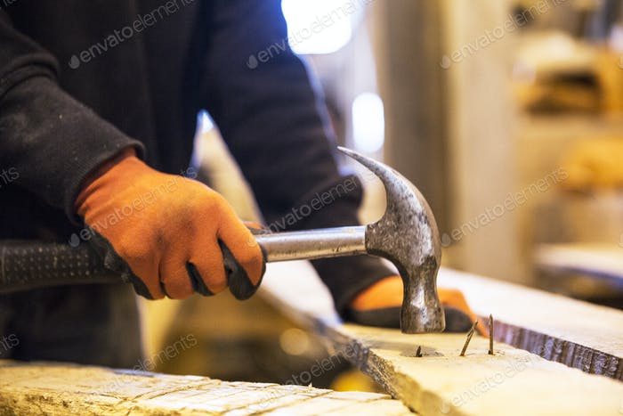 Close up of person wearing work gloves holding, hammer, removing rusty nails from recycled wooden