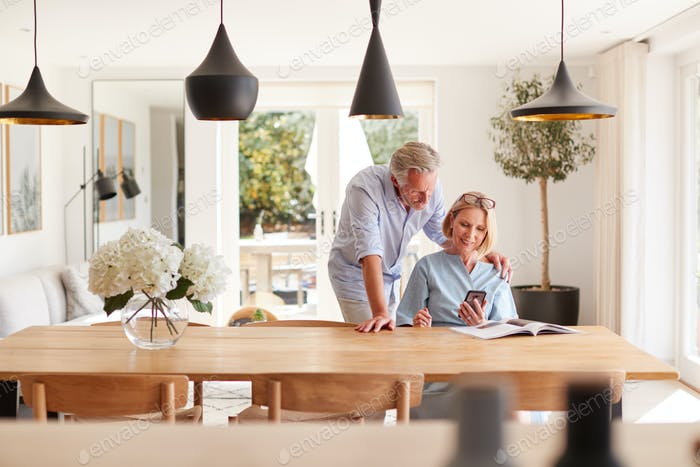 Senior Couple Relaxing With Magazine At Home Looking At Mobile Phone Sitting At Dining Room Table