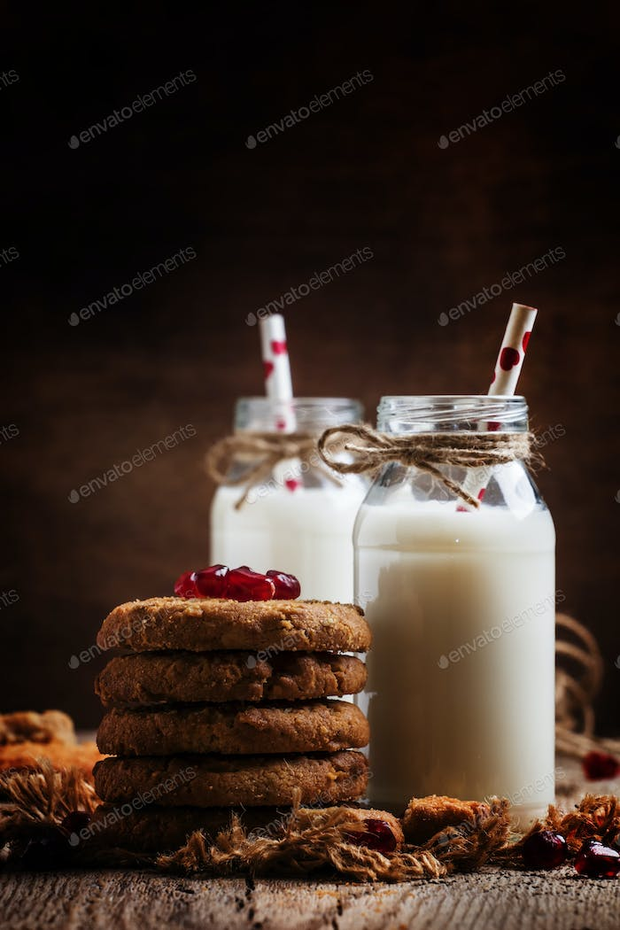 Milk beverages in glass bottles, crisp cookies with pomegranate seeds