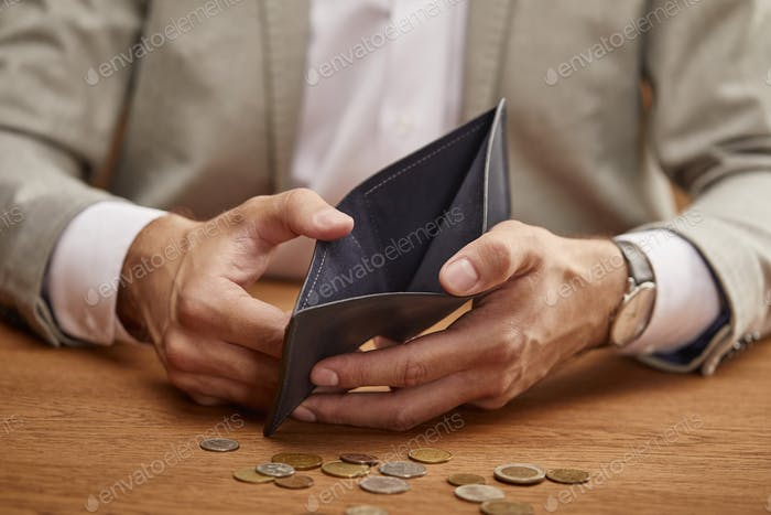 partial view of man showing empty wallet near coins on wooden table