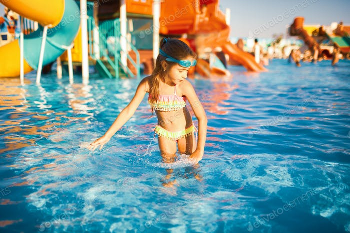A cheerful girl in blue goggles for swimming whirls in a pool with clear clear water with her hands