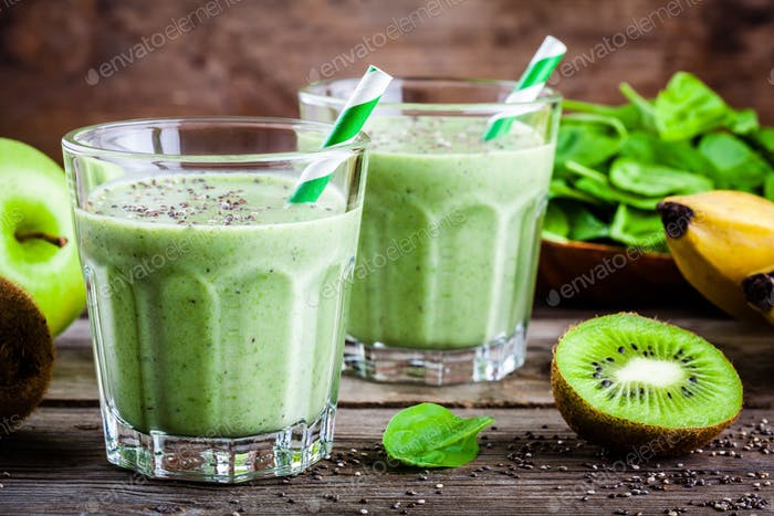 healthy green smoothie with apples, banana, kiwi, avocado, spinach and chia seeds in glass