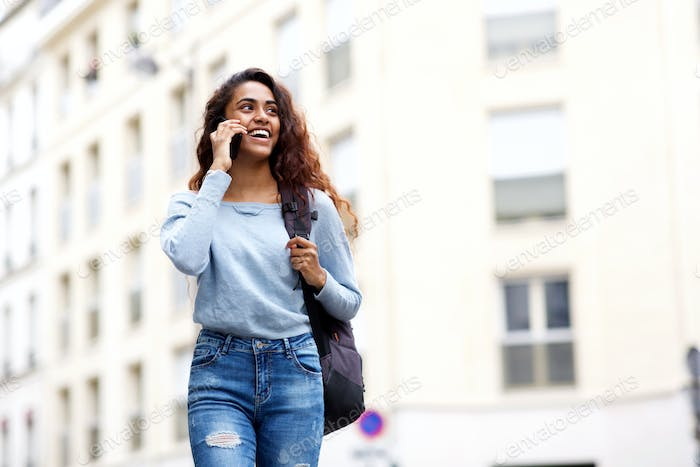 happy young woman walking and talking with cellphone and bag in city
