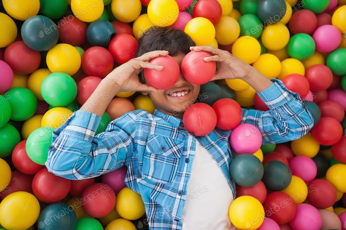 Cute boy smiling in ball pool at a party