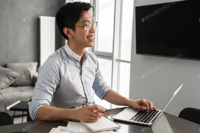 Portrait of a cheerful young asian man using laptop
