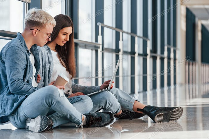 Young male and female students sitting together on the floor with laptop