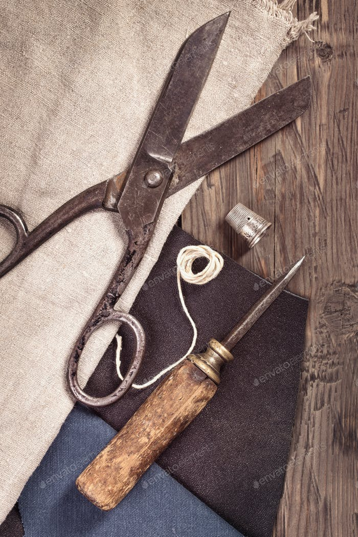 Vintage scissors, awl and thimble with leather and cloth