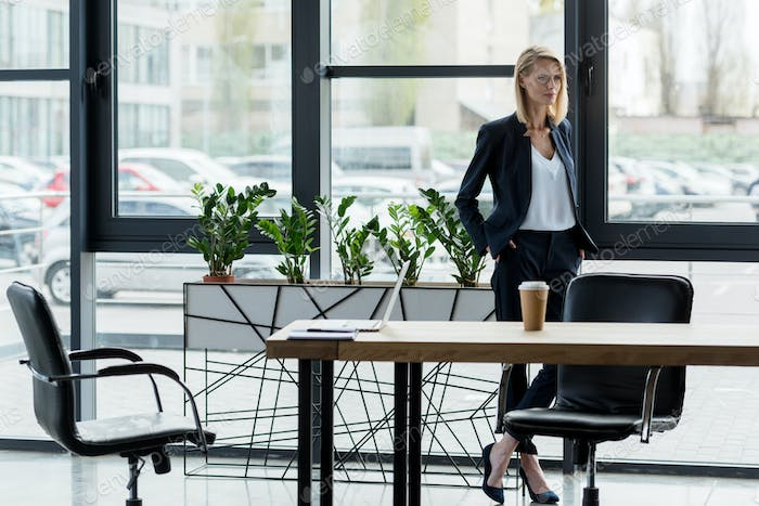 confident businesswoman standing with hands in pockets and looking away in office