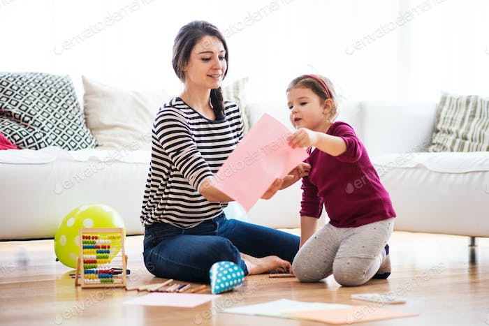 Young mother with a small girl at home, drawing.