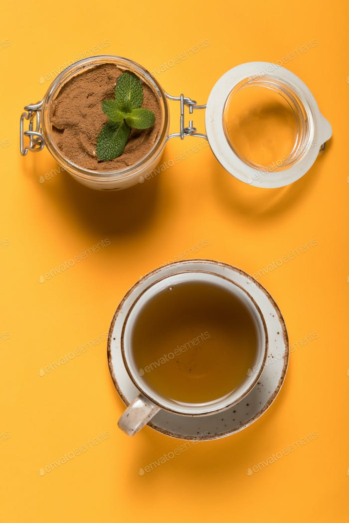 Sweet cold dessert with tea on a colored background