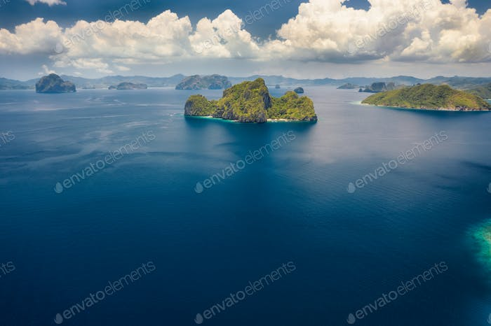 Aerial view the Entalula Island from the distance. Open ocean, white clouds at high altitude. Bacuit