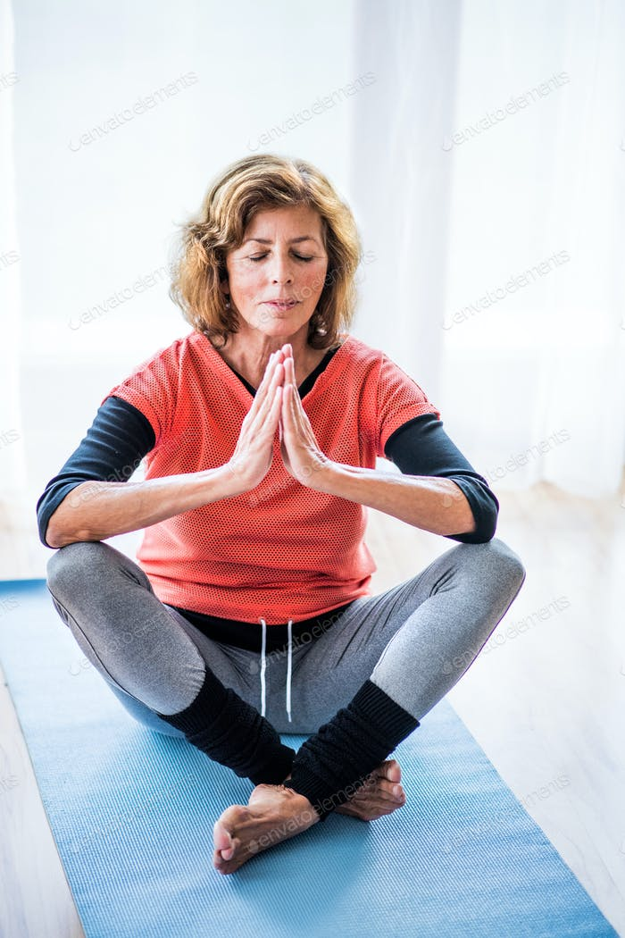 A contented senior woman meditating at home.