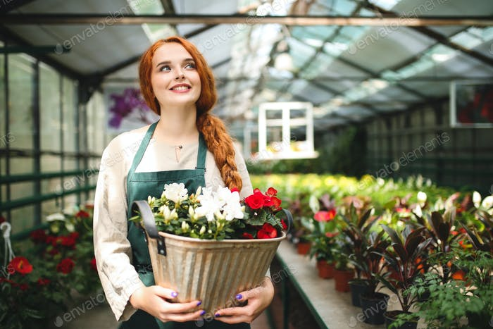 Cute smiling florist in apron standing and holding flowers in metal pot joyfully looking aside