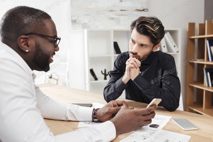 Joven hombre de negocios sentado cuidadosamente mirando a su socio de negocios multinacional