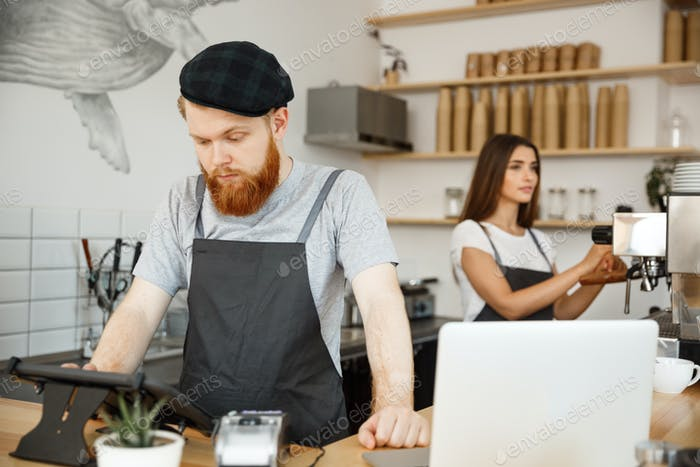 Coffee Business Concept - Young handsome bearded bartender, barista or manager posting the order