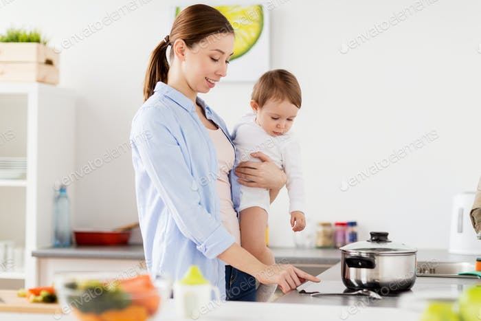 happy mother and baby cooking at home kitchen