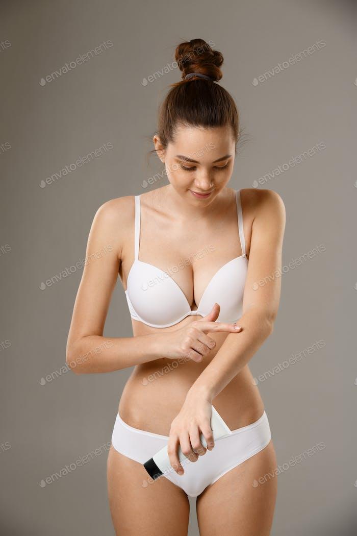 Woman applying skin moisture creme