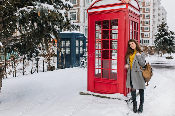 Outdoor portrait of fashionable brunette girl with backpack posing beside red call-box during weeken