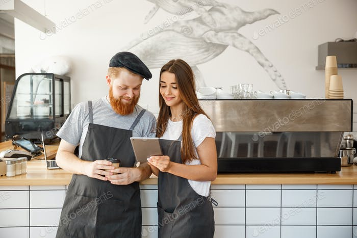 Coffee Business Concept - Cheerful baristas looking at their tablets for online orders