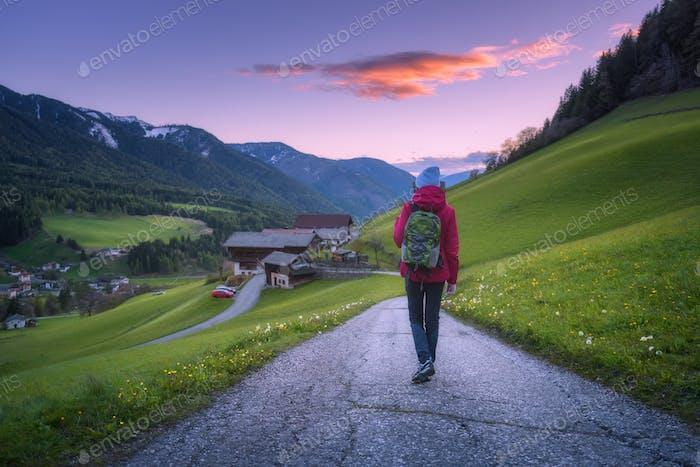 Mujer joven con mochila está de pie en el camino de la montaña
