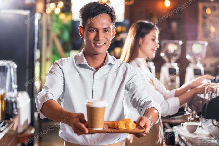 Asian Coffee shop owner serving bakery cake and coffee cup to customer in coffee shop