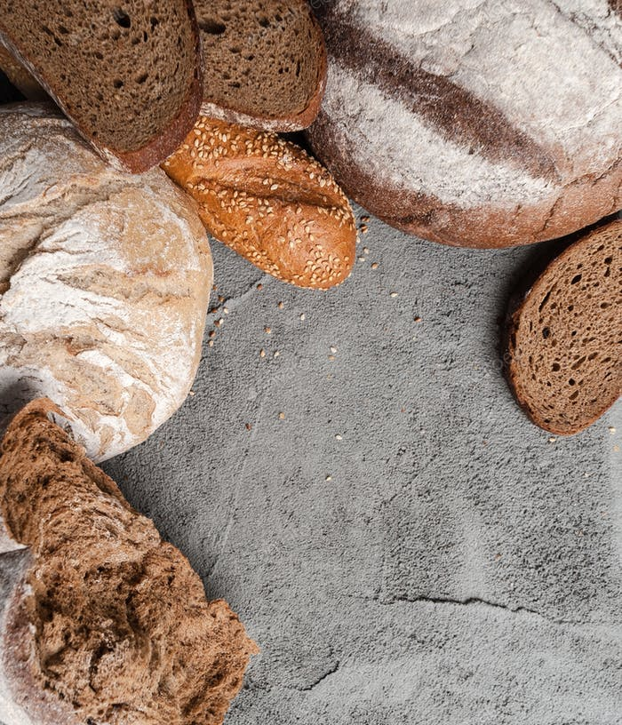 Different types of bread on the concrete top with a place for te