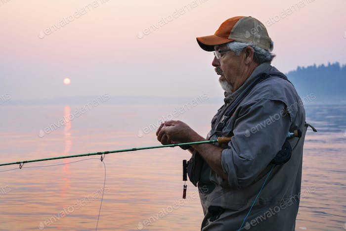 Caucasian man tying a fly on his fly fishing line while fishing for salmon and searun cutthroat