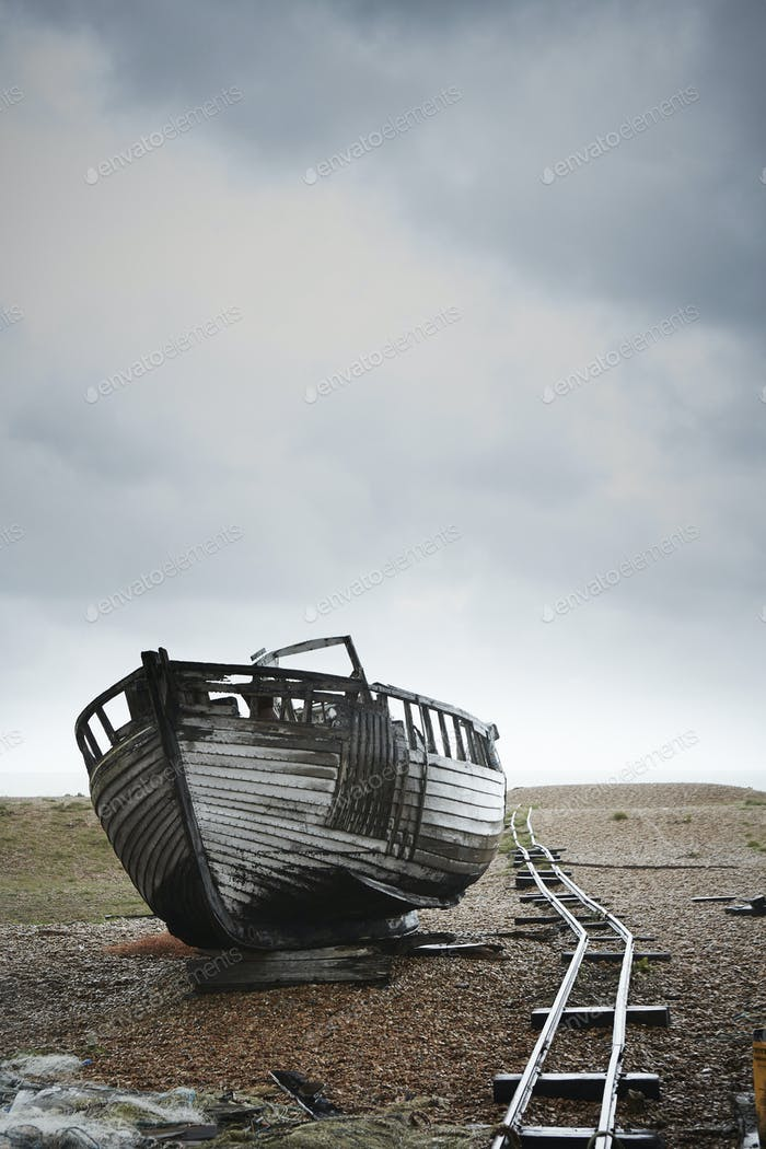 Abandoned wooden boat beached on the shingle by an old narrow gauge track.