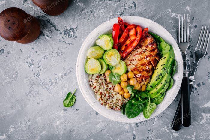Vegetable bowl with grilled chicken and quinoa, spinach, avocado, brussels sprouts and chickpea