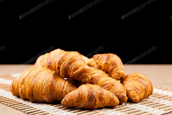 Freshly baked croissants lying on a table