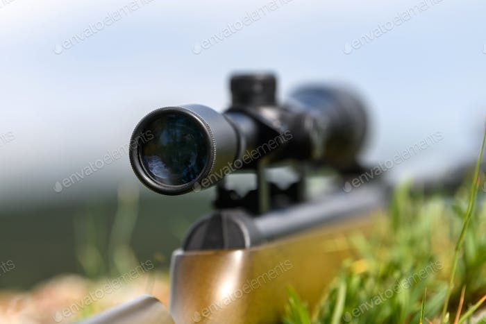 Rifle scope on the street with blurry background. Hunting concept