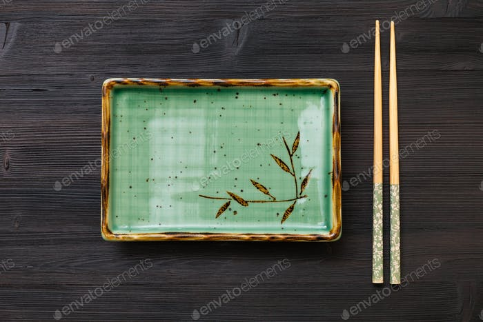 above view of square plate and chopsticks on brown