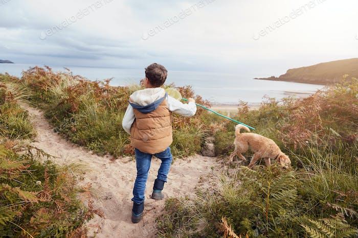 Boy Carrying Fishing Net Exploring Sand Dunes With Pet Dog