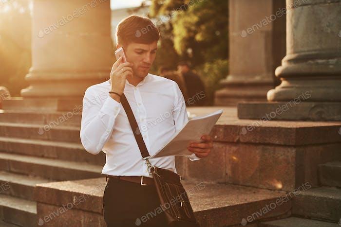 Lesen Sie das Dokument sorgfältig durch. Geschäftsmann in formeller Kleidung mit Dokumenten ist in der Stadt