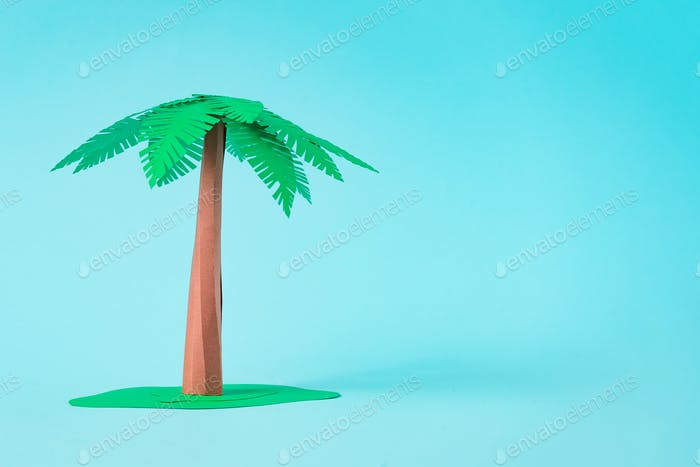 Palm tree made of paper on pastel blue background. Minimal summer beach concept.
