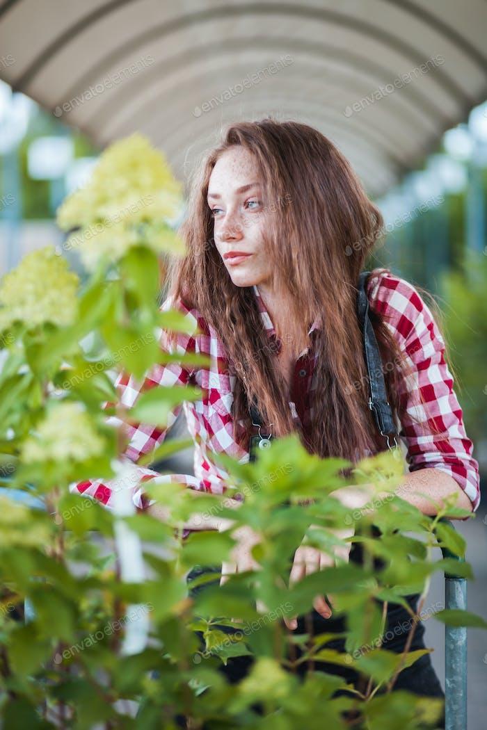 Gardener woman with shopping cart choosing plants in a garden center