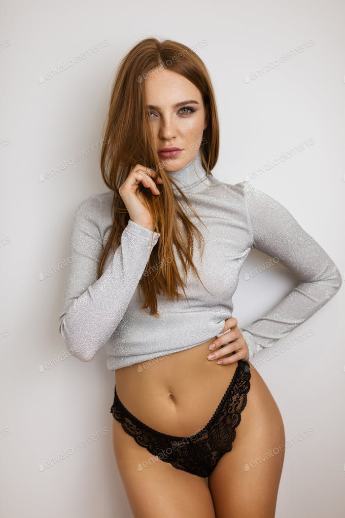 Lady standing in black lingerie and gray turtleneck thoughtfully looking in camera on white wall