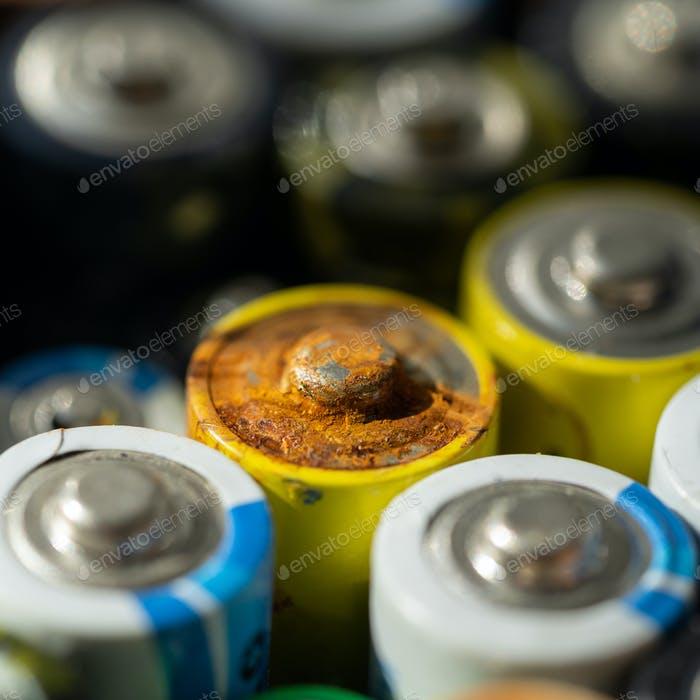 discharged batteries of different sizes and formats, used battery with corrosion and rust