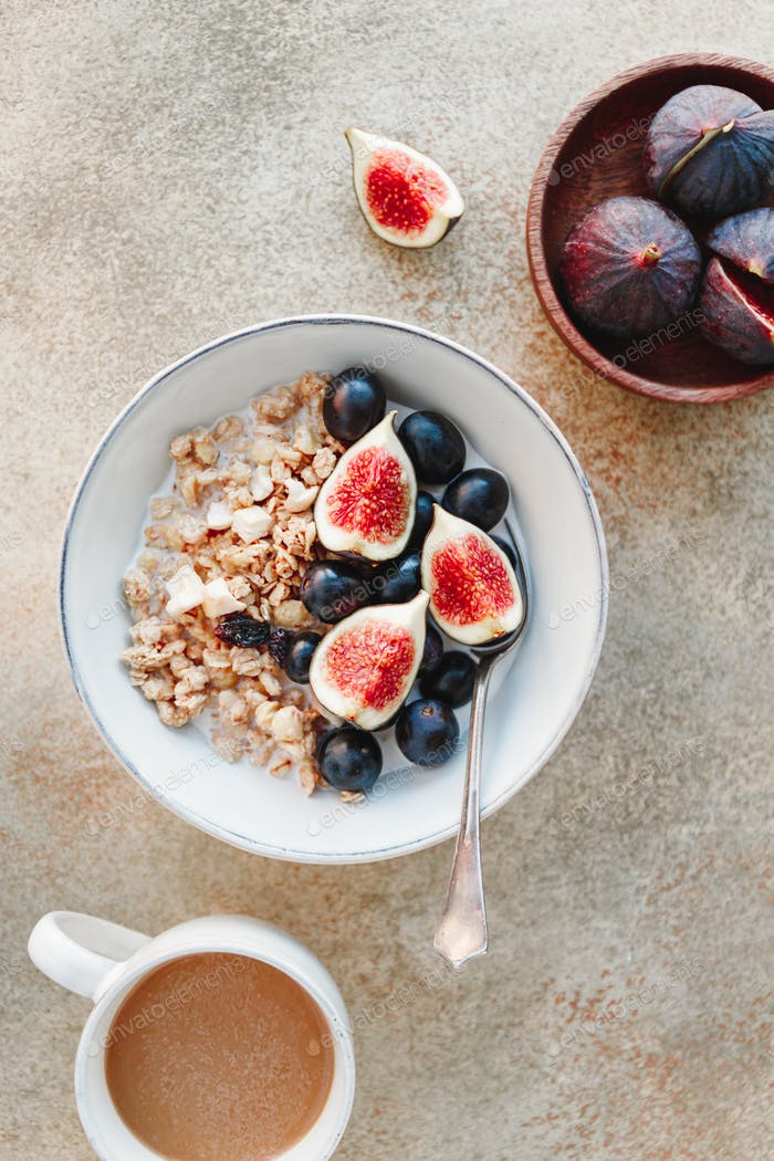 Breakfast bowl with granola, blue grape and fig slices.