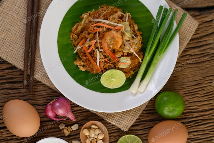 Padthai shrimp in a white dish with lime and eggs on wooden table.