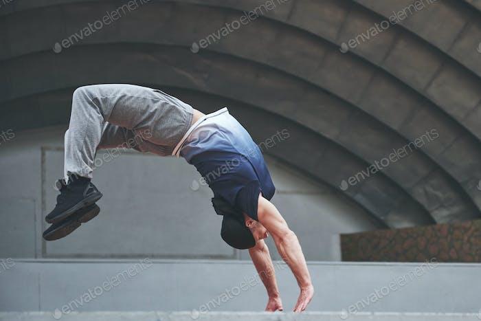 The man outdoors practices parkour, extreme acrobatics