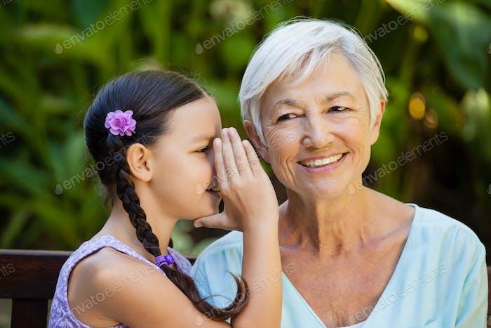 Granddaughter whispering in ears of smiling grandmother