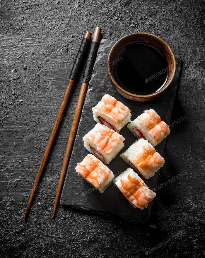 Frische Sushi-Rollen mit Garnelen auf einem Stand mit Sojasauce und Stäbchen.