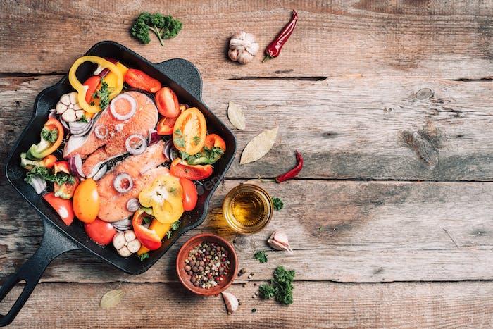 Filete de salmón con verduras en sartén a la parrilla sobre fondo de madera. Vista superior. Filete de salmón crudo con