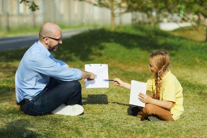 Nettes Schulmädchen Studieren mit Lehrer im Freien