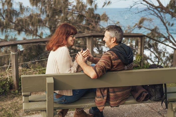 Paar mittleren Alters sitzt auf der Bank im Park und trinkt Tee.